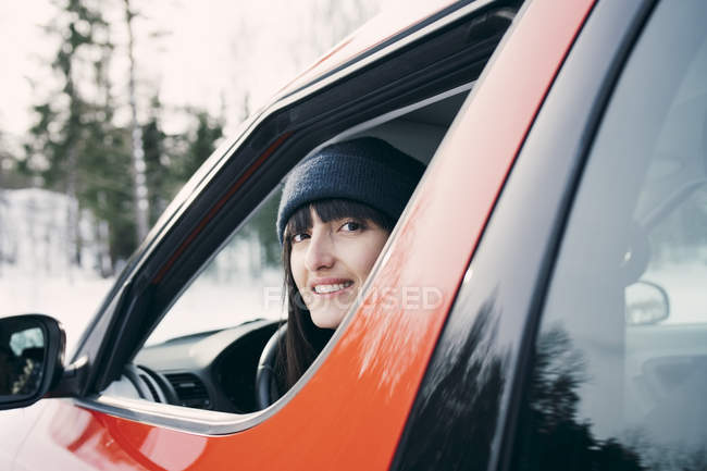 Portrait of smiling woman sitting in red car — Stock Photo