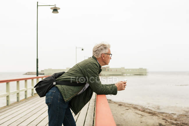 Side view of senior man leaning on railing while looking at sea against clear sky — Stock Photo