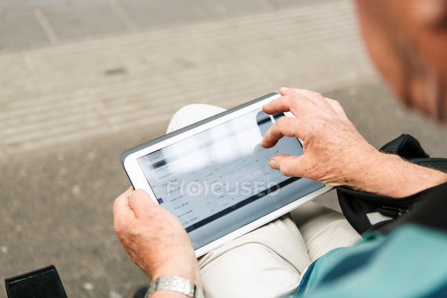 High angle view of senior man using digital tablet while sitting in city — Stock Photo
