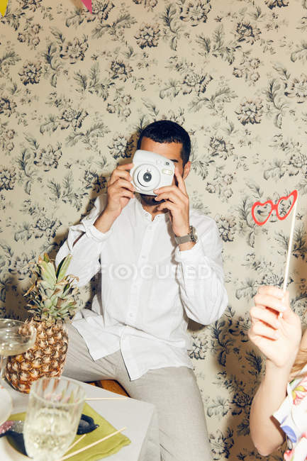 Young man photographing while sitting during dinner party at home — Stock Photo
