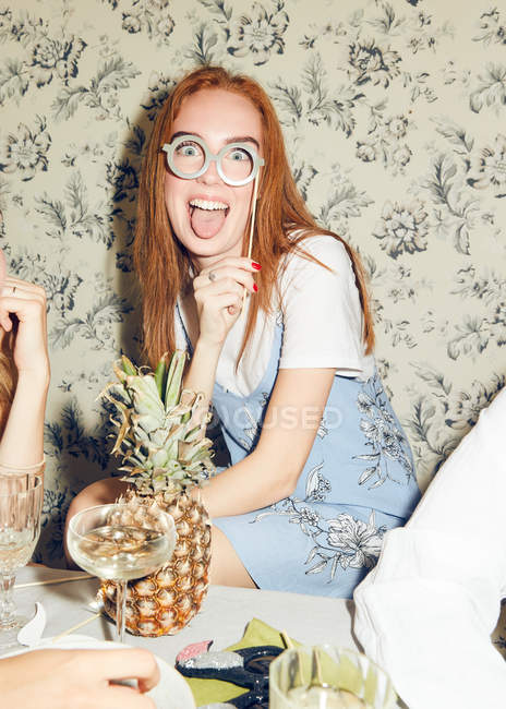 Portrait of young redhead woman holding prop while sitting amidst friends during dinner party at home — Stock Photo