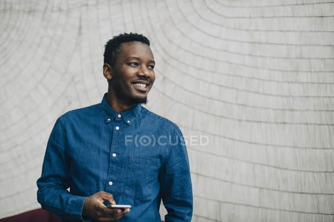 Uomo d'affari sorridente che tiene il telefono cellulare mentre guarda lontano contro il muro grigio — Foto stock