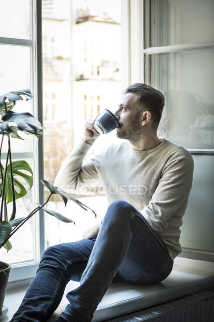 Thoughtful young man drinking coffee while sitting on window sill — Stock Photo