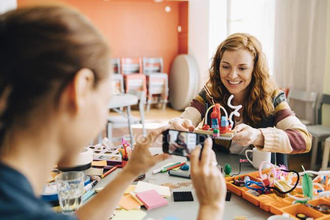 Empresaria fotografiando colega femenina sonriente sosteniendo juguete en la mesa en la oficina creativa - foto de stock