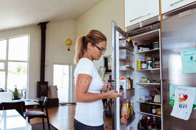 Side view of woman using mobile phone while standing by open refrigerator at kitchen — Stock Photo