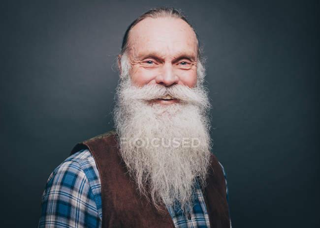 Retrato de sonriente hombre mayor con barba blanca y bigote sobre fondo gris - foto de stock