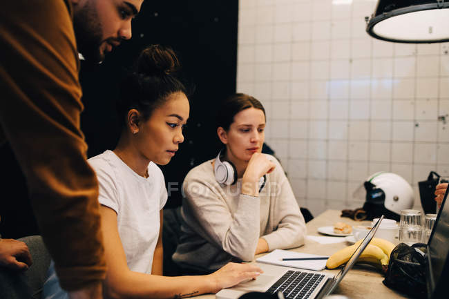 Confident young multi-ethnic colleagues discussing over laptop at office — Fotografia de Stock