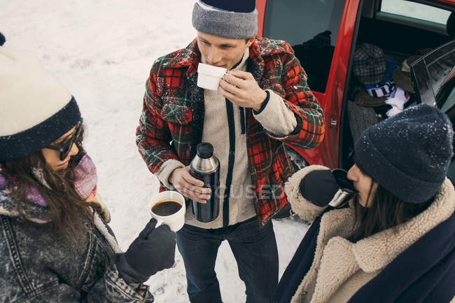 High angle view of friends having coffee while talking by car on snow — Stock Photo