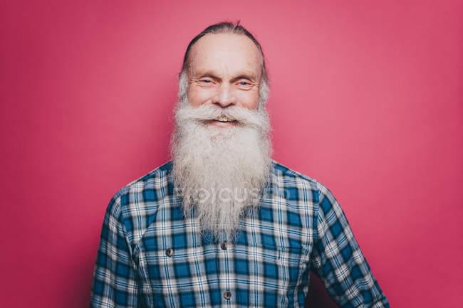 Retrato de sonriente hombre senior con larga barba blanca sobre fondo rosa - foto de stock