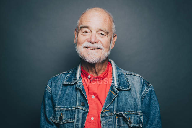 Portrait of smiling senior man wearing denim jacket against gray background — Stock Photo