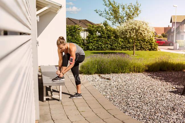 Frau bindet bei sonnigem Tag Schuhe auf Bank im Hinterhof — Stockfoto