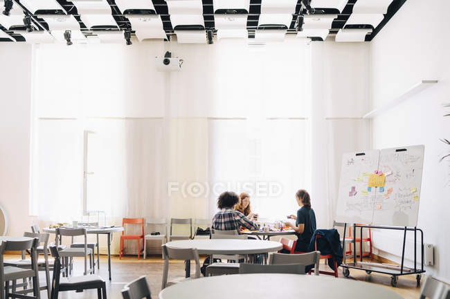 Multi-ethnic team of technicians working at table by whiteboard in creative office — Stockfoto