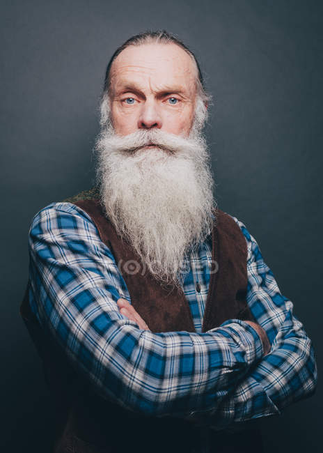 Portrait of confident bearded senior man standing arms crossed over gray background — Stock Photo