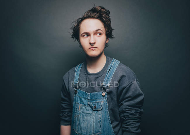 Young man wearing overalls while looking sideways over gray background — Stock Photo