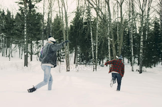 Playful friends running by trees on snow covered landscape — Stock Photo