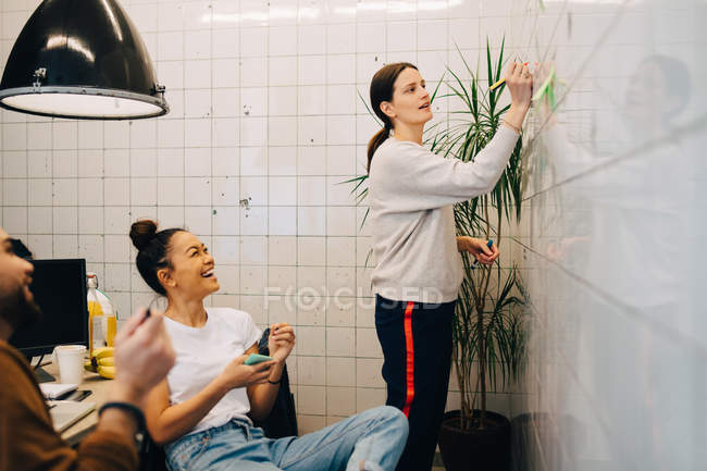 Smiling colleagues looking at young businesswoman writing strategy on tile wall in creative office — Stock Photo
