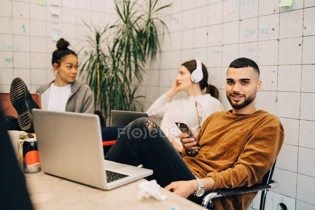 Portrait of smiling young businessman holding smart phone while sitting with female colleagues at small office — Foto stock