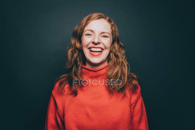 Retrato de mulher no topo laranja rindo contra fundo cinza — Fotografia de Stock