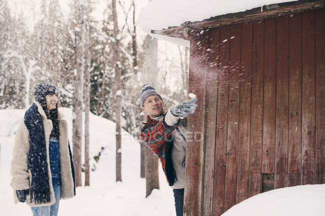 Friend looking at man throwing snowball while standing behind log cabin during winter — Stock Photo