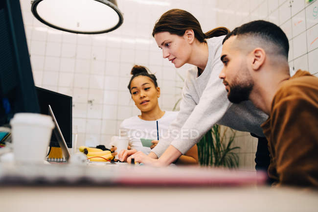 Young businesswoman using laptop while standing amidst colleagues at creative office — Stock Photo
