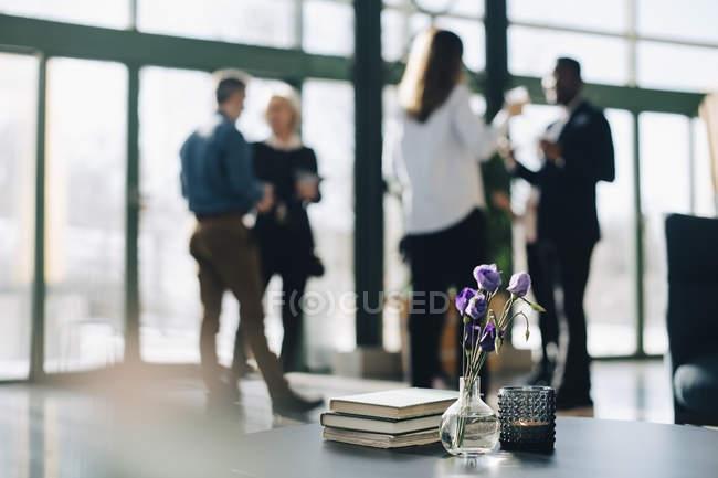 Крупный план вазы и дневники на столе с деловыми людьми в фоновом режиме — стоковое фото