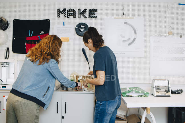 Female business colleagues working over cabinet in creative office — Stockfoto