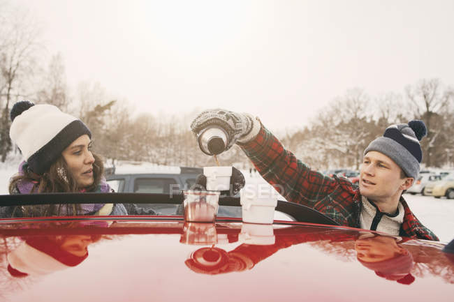 Friend looking at man pouring coffee in cup over car hood — Stock Photo