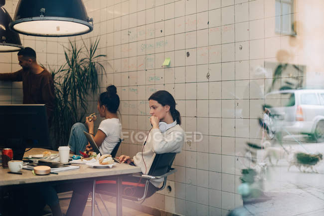 Young businesswoman using laptop while colleagues discussing at creative office seen through window — Stock Photo