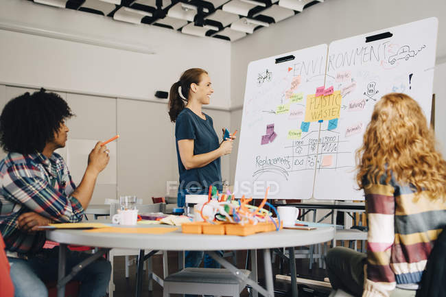 Smiling businesswoman explaining plastic waste management plan to technicians over whiteboard at creative office — Stockfoto