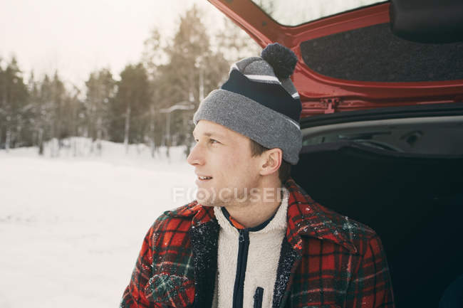 Close-up of thoughtful man looking away while sitting in car trunk — Stock Photo