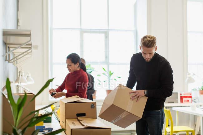 Jeune homme d'affaires arrangeant la boîte en carton par des collègues féminines travaillant dans un bureau créatif — Photo de stock