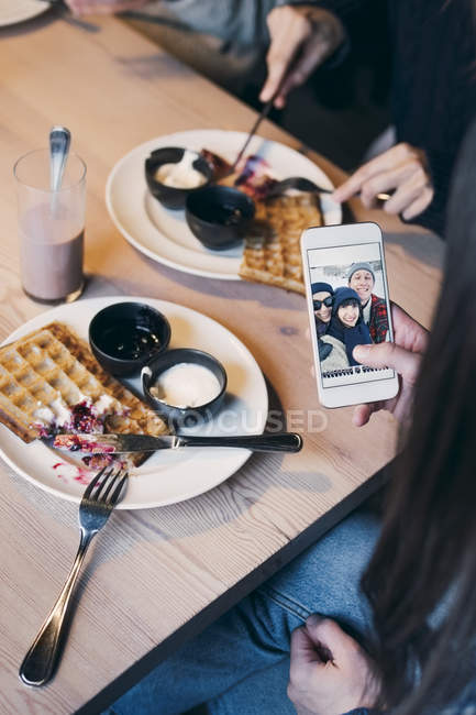 Cropped image of woman looking at photograph on smart phone screen while having breakfast with friends — Stock Photo