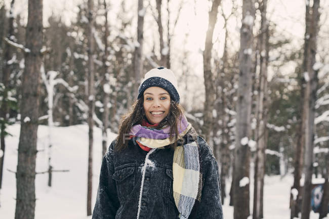 Portrait of smiling mid adult woman standing against bare trees during winter — Stock Photo