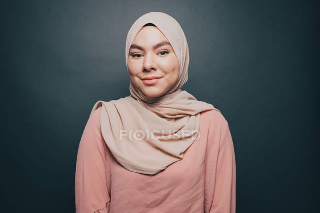 Портрет улыбающийся молодой женщины в хиджабе сером фоне — стоковое фото