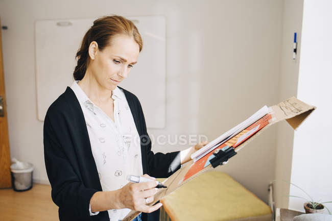 Confident businesswoman writing strategy on placard at creative office — Stockfoto