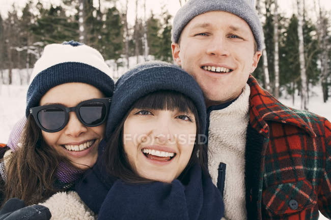Portrait of cheerful friends wearing knit hats at park during winter — Stock Photo