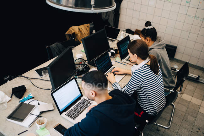 High angle view of young multi-ethnic hackers programming on laptops at desk in small office — Foto stock