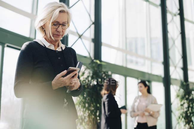 Donna d'affari anziana che utilizza il telefono cellulare mentre i colleghi comunicano in background — Foto stock