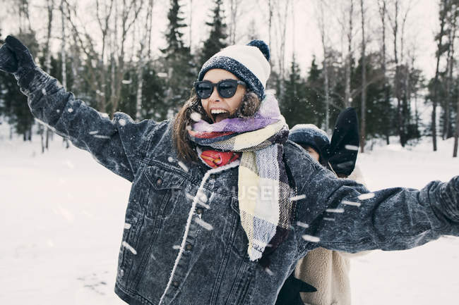 Happy woman enjoying with friend at snowy field — Stock Photo