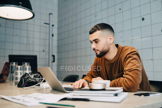 Confident young male computer programmer using laptop at desk in small office — Stock Photo