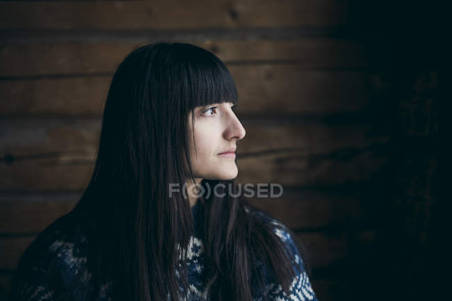 Close-up of thoughtful woman looking away at log cabin — Stock Photo