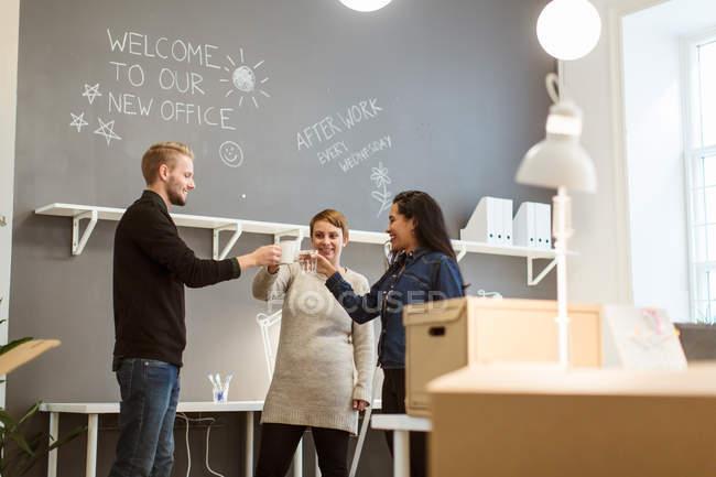 Низький кут зору щасливих багатоетнічних колег тостів напоїв, стоячи проти стіни в творчому кабінеті — стокове фото