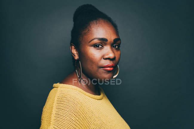 Портрет уверенно середине взрослая женщина над серый фон — стоковое фото
