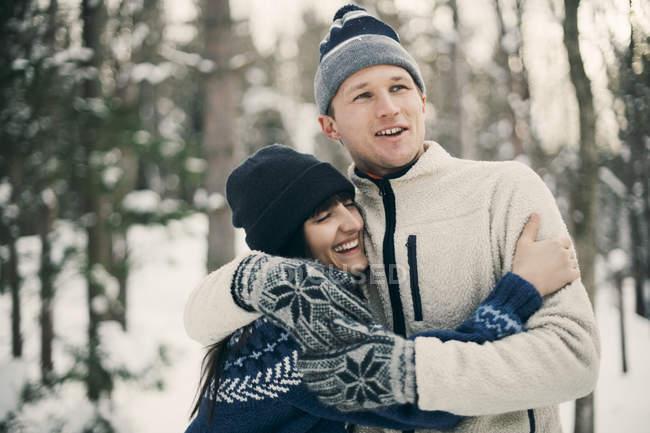 Glückliche Freunde, die sich im Winter im Park umarmen — Stockfoto