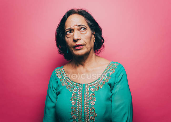 Thoughtful senior woman looking up against pink background — Stock Photo