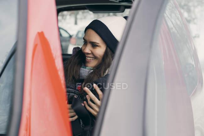 Smiling mid adult woman sitting in car seen through open door — Stock Photo