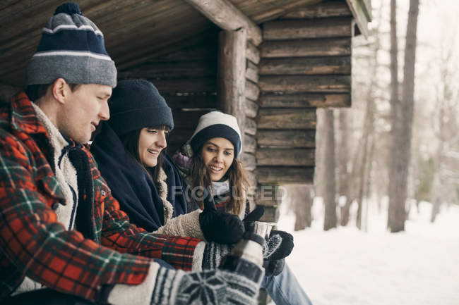 Man giving drink to female friends while sitting at log cabin during winter — Stock Photo