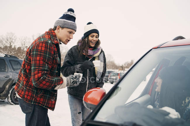 Happy man and woman having coffee while talking to friend sitting in car during winter — Stock Photo
