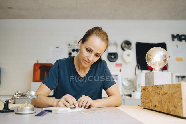 Selbstbewusste Technikerin, die im kreativen Büro an der Werkbank sitzt — Stockfoto