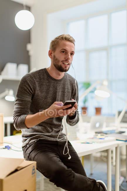 Giovane uomo d'affari che distoglie lo sguardo mentre parla su smart phone attraverso le cuffie presso l'ufficio creativo — Foto stock